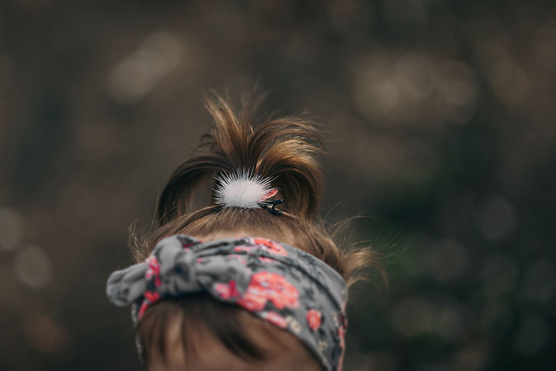 A girl with short dark hair, a fluffy white hairpin and a violet headband