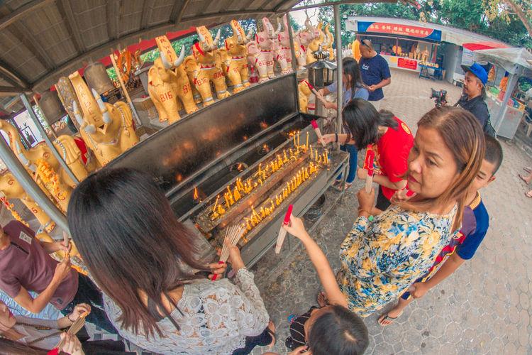 Hat Yai, Thailand – 1 May 2018: Buddhist devotee lighting a stick with a candle at Hat Yai Municipal Park. ASIA Buddha EyeEm Best Shots Hat Yai Thailand Travel Devotee Eyemphotography Hat Yai Municipal Park