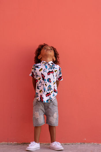 Upwards Child Childhood Full Length Standing One Person Offspring Curly Hair Front View Colored Background Hairstyle Casual Clothing Looking Innocence Brown Hair Day