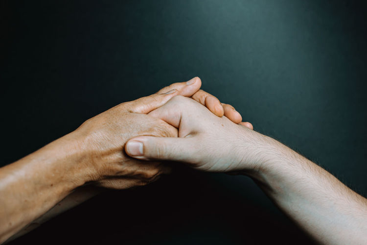 Close-up of couple holding hands against black background