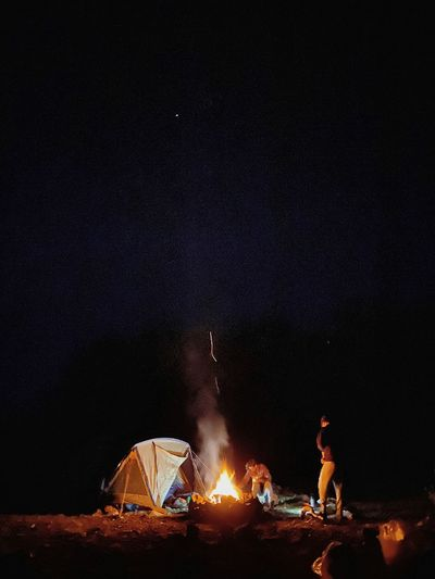 People relaxing on fire at night