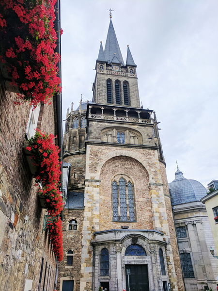 Red Flowers and Cathedral Architecture History Travel Destinations Built Structure Building Exterior Clock Tower Business Finance And Industry No People City Day Outdoors Politics And Government Sky Clock Face cathedral church government building red flowers steeple church steeple