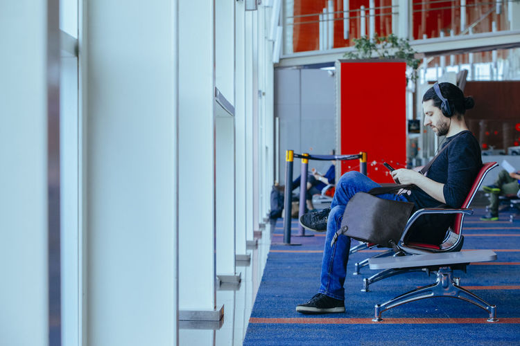 Side view of man sitting on chair at airport