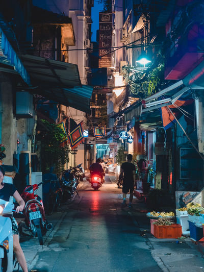 Architecture Building Exterior City Built Structure Illuminated Transportation Direction Street Night Women Real People Group Of People The Way Forward Market Retail  Building Incidental People Men Mode Of Transportation Market Stall Outdoors Street Market