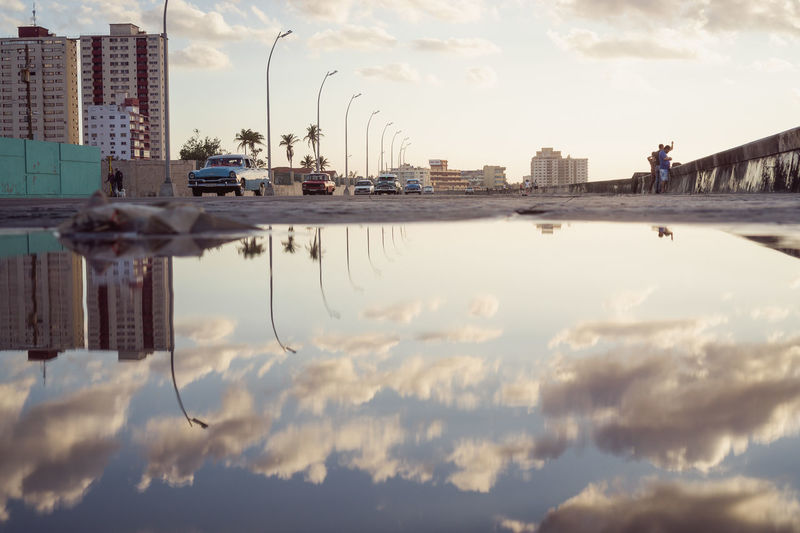 Malecón, Havana, Cuba Been There. Cars City Life Cuba Havana Lifestyle Malecon Architecture Car City Cityscape Cloud - Sky Enjoying Life Eye4photography  Puddle Reflection Sky Skyscraper Street Streetphotography Sunset Travel Destinations Urban Skyline Vintage Cars Water