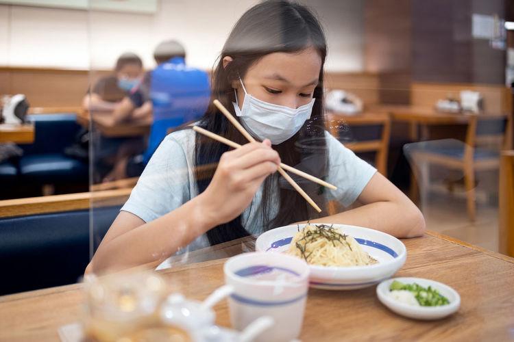 Girl eating food in restaurant