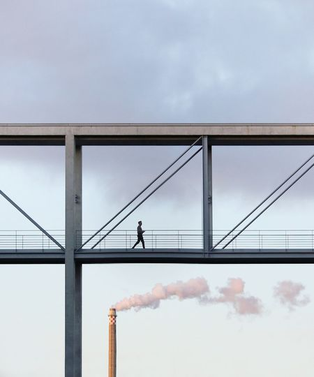 Low angle view of man walking on bridge