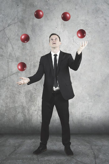 Businessman Juggling Red Balls Against Wall
