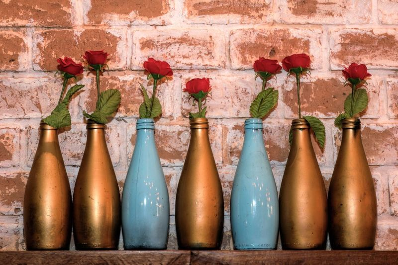 Close-Up Of Red Roses In Bottles On Shelf