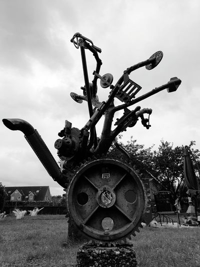 Old machinery on field against sky
