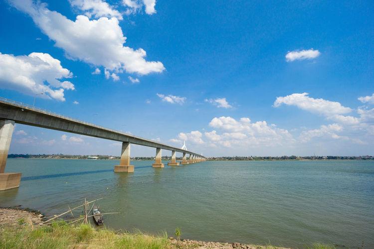 Bridge over calm river against sky