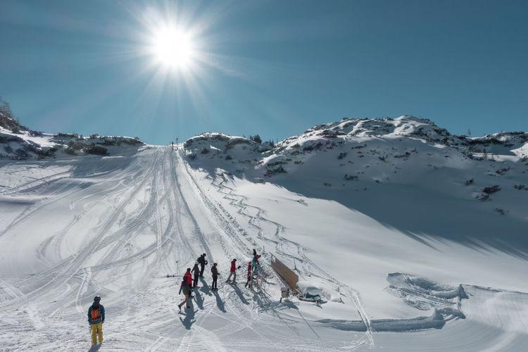 People on ski slope on sunny day