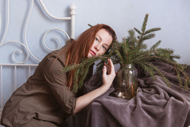 Portrait of young woman holding plant