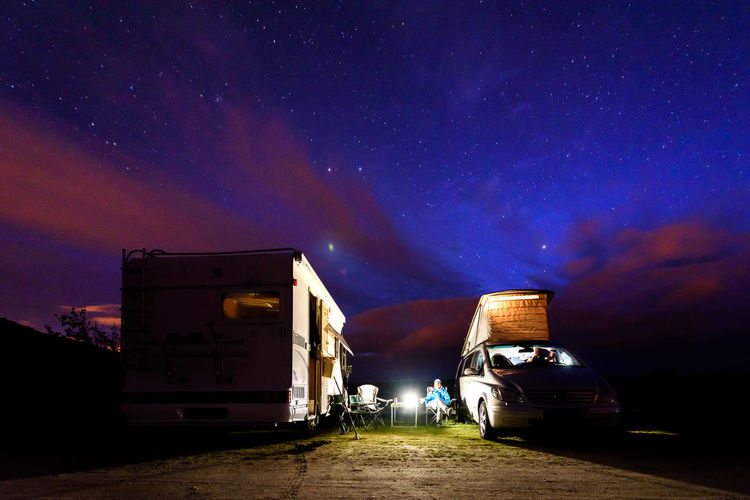 Motor home on field against sky at night