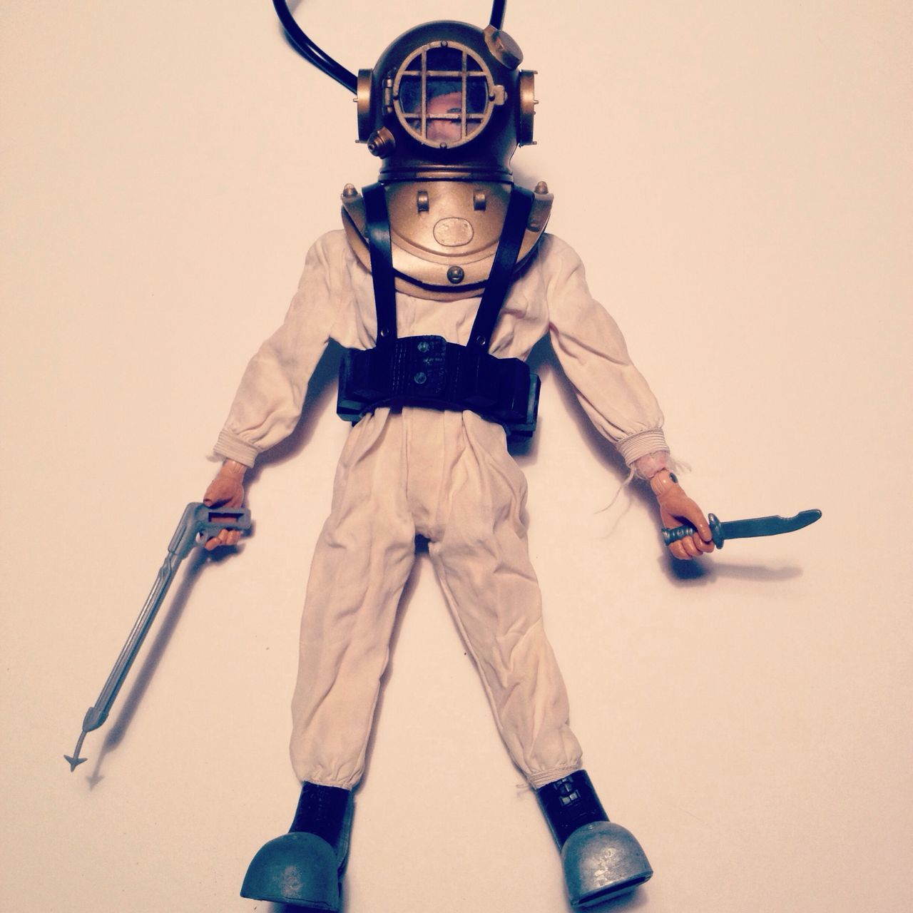 Toy man wearing retro diving suit over white background