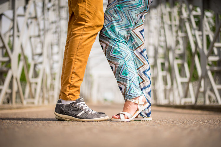 Low section of couple standing on road