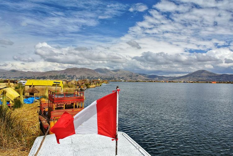 Scenic view of flag by lake against sky