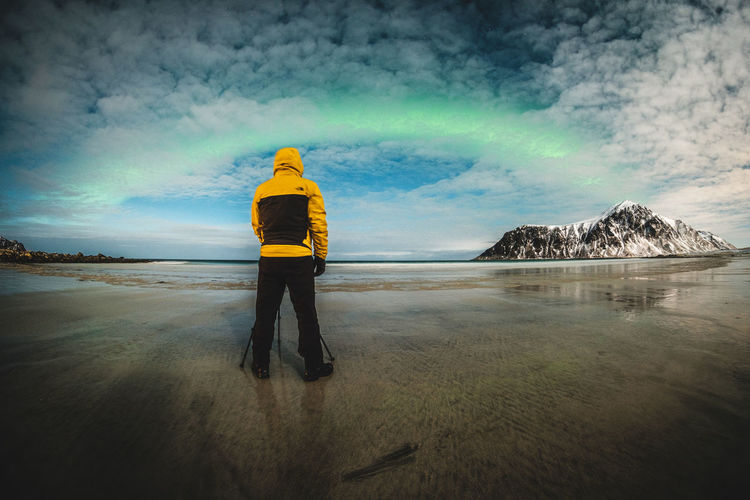 The photographer looking to aurora borealis on the cloudy sky. 2018 In One Photograph Aurora Borealis Photographer Cloud - Sky Cloud Sky One Person Beauty In Nature Rear View Water Real People Full Length Standing Nature Scenics - Nature Land Tranquil Scene Men Environment Tranquility Day Lifestyles Outdoors Warm Clothing Power In Nature
