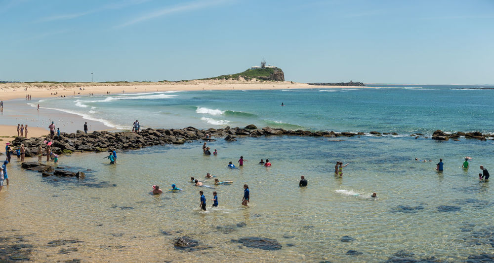 Surf beach with bathers and lighthouse on headland in background Beach Coast Coastline Horizon Over Water Ocean Outdoors Panorama Sand Sea Seascape Shore Summer Surf Tropical Climate Vacation Vacations Water Wave Weekend Activities
