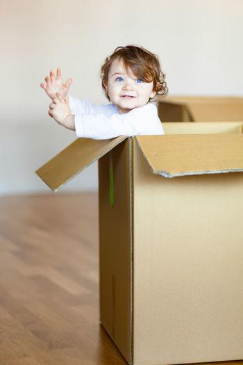 Cute girl with blue eyes in cardboard box