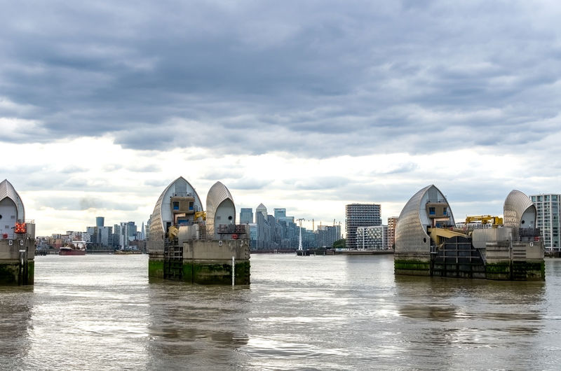 View of city buildings by river against cloudy sky