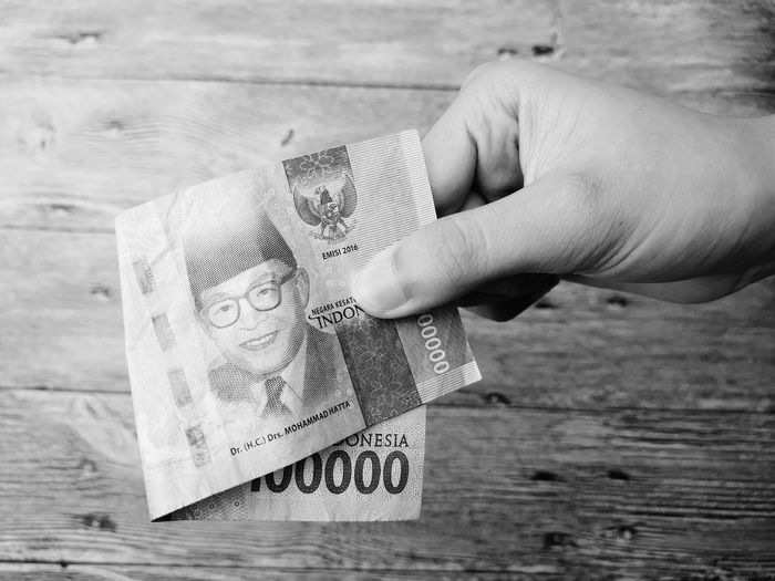 Hand giving a INDONESIA rupiah money with wooden background and black and white photoghpy. Background Color Abstract Black Shadow LINE Art Attraction Black And White INDONESIA Money Money Money EyeEm Selects Human Hand Close-up Human Finger Finger Chance Personal Perspective