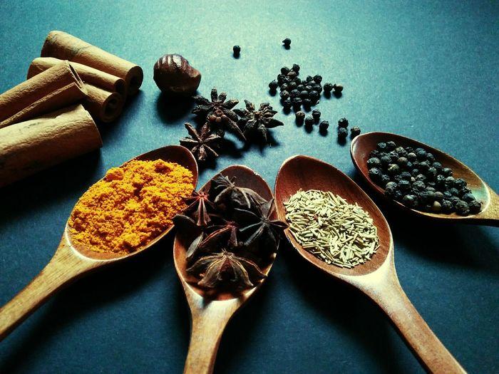 Various ingredients in wooden spoons on table