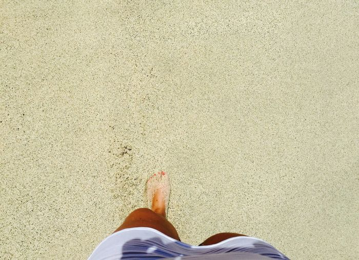 Low Section View Of Woman Feet In Sand