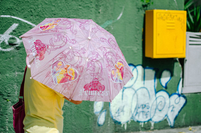 Princess. One Person Focus On Foreground Day Clothing Creativity Graffiti Yellow Close-up Art And Craft Floral Pattern Outdoors Real People Standing Women Holding Human Body Part Nature Pink Color Midsection Umbrella Streetphotography EyeEm Best Shots EyeEm Selects The Art Of Street Photography