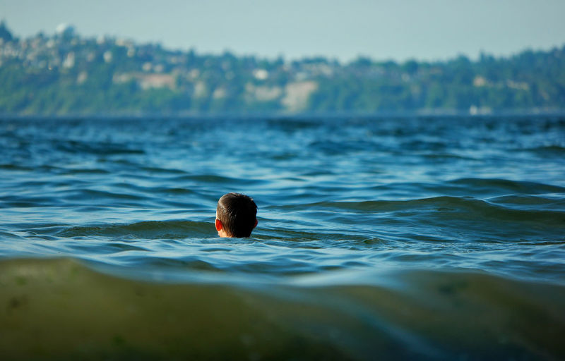 Rear View Of Boy Swimming In Lake