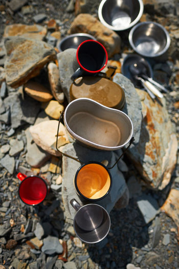 High angle view of empty coffee cups on rocks at campsite