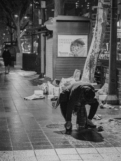 Rear view of man sitting on sidewalk