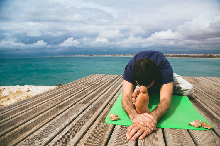 Full Length Of Man Performing Yoga On Jetty Over Sea Against Cloudy Sky