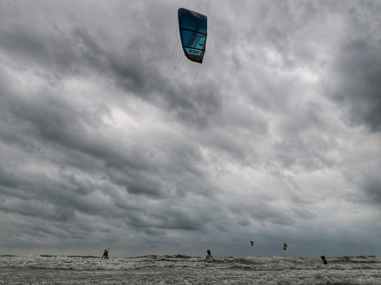 cloud - sky, sky, sea, nature, sport, overcast, leisure activity, water, horizon, beauty in nature, horizon over water, day, scenics - nature, land, adventure, group of people, outdoors, unrecognizable person, kiteboarding