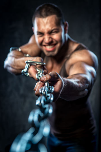 Muscular worker pulling metal chain while standing against black background