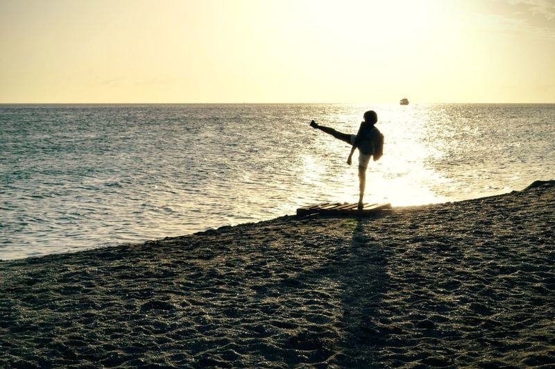 Woman kicking on shore at beach against sky