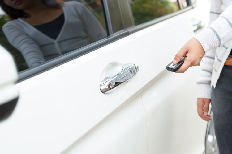 Midsection of woman opening car with remote control key