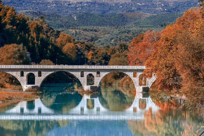 Arch bridge over river during autumn