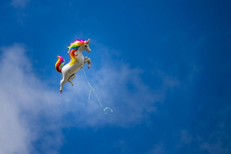 Low angle view of toy flying against blue sky