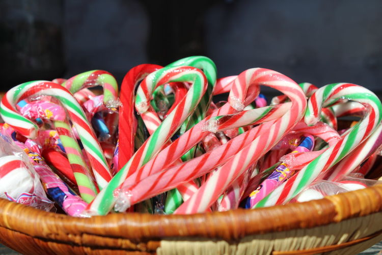 Close-up of multi colored candy canes in wicker basket