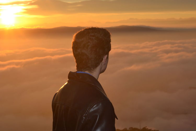 Man looking at view against cloudy sky during sunset