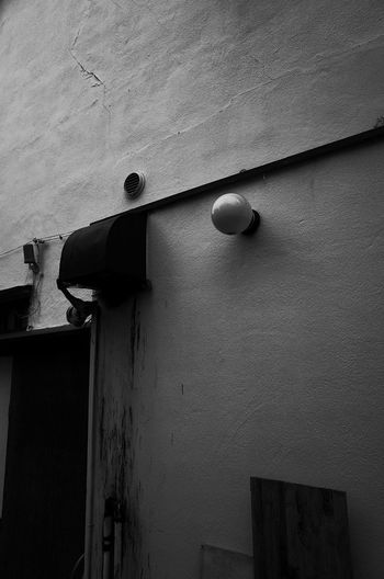 Low angle view of electric lamp on wall of old building