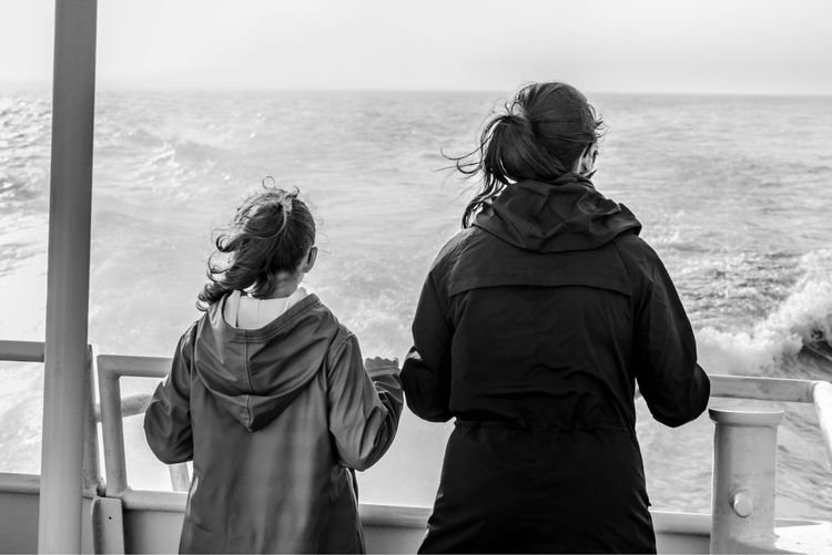 Rear View Of Daughter And Mother Looking At Sea While Standing By Railing In Ship