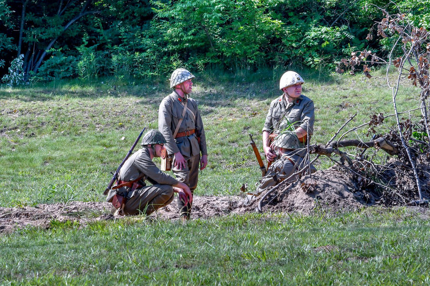 June 22 2018 St Joseph MI USA ; soldiers wearing vintage korean uniforms hide behind brush during a mock battle reenactment in Michigan USA American Military Event Field Fight Korean War Lest We Forget Nature Soldiers Uniforms Active Adults America Editorial  Historiacl Reenactment History Men Military Outdoors People Reenactment Role Playing St Joseph MI USA Vietnam War Era War Weapon
