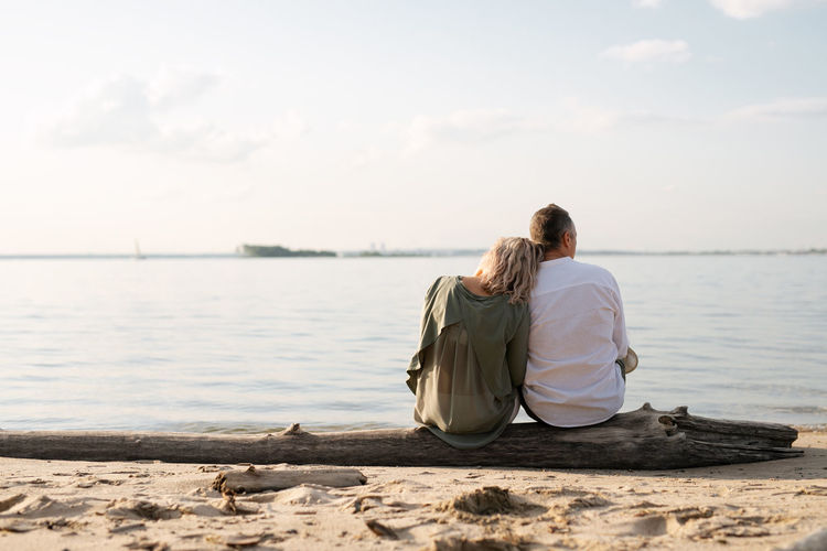 A man and a woman are sitting on a log by the sea