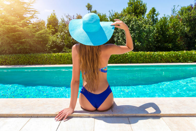 Beautiful, blonde woman wearing a bikini relaxes by the poolside on a hot summer day Blonde Hair Hat Relaxing Vacations Bikini Blue Clothing Concept Hat Leisure Activity Lifestyles Model One Person Pool Poolside Rear View Summer Sun Hat Sunlight Swimming Pool Swimwear Turquoise Colored Water Women