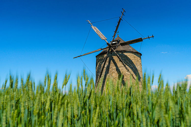 Traditional windmill on field against blue sky