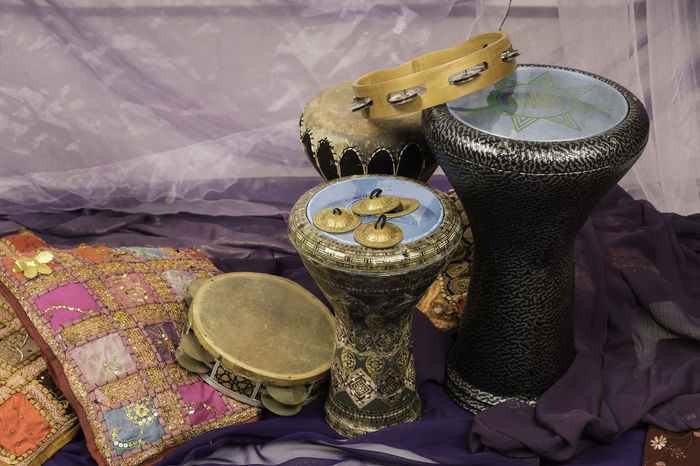Side view of musical instruments of a bellydance percussiongroup with darbuka's, tambourines and zills Arabic Music Belly Dance Celebration Arabic Style Close-up Cushion Cymbal Darbuka Doumback Drum Drums Flower Gold Colored High Angle View Indoors  Making Music Music Musical Instrument No People Purple Side View Still Life Tambourine Togetherness Tomtom Zills