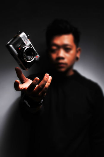 Young man photographing against black background