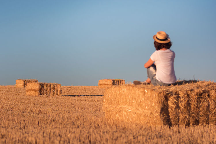 Woman Sitting On Hay Bale Against Clear Sky